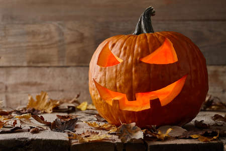 Carved Halloween pumpkin on wooden planks, holiday decoration