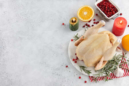 Raw turkey or chicken and ingredients for cooking on white table. Holiday preparation.