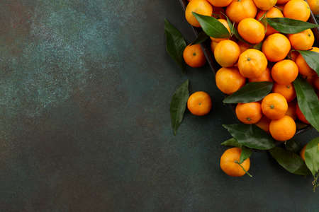 Fresh mandarin oranges with leaves, copy space. Seasonal winter fruits for Christmas.