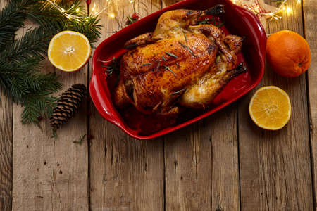Roasted chicken on wooden rustic table for Christmas dinner