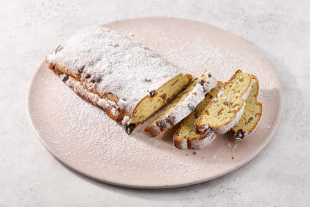 Traditional Christmas stollen dessert with candied fruit on plate. Holiday winter bread. Standard-Bild
