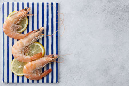 Cooked tiger prawns on blue and white rectangular plate, copy space