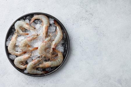 Fresh tiger prawns in plate with ice on white textured background, top view Standard-Bild