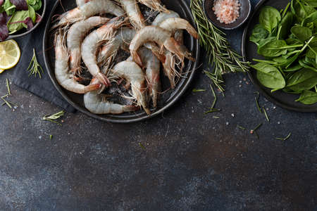Raw tiger prawns on metal textured background, copy space