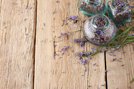 Dried lavender in glass jars on wooden background