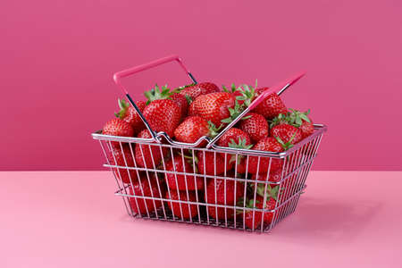 Fresh strawberries in shopping basket on pink background, all in focus