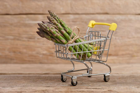 Fresh green asparagus in shopping basket, spring vegetables grocery and food market concept