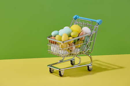 Colorful Easter sweets in shopping basket on green and yellow background, holiday concept