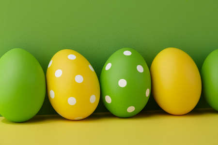 Painted Easter eggs on green and yellow background, spring holiday preparation