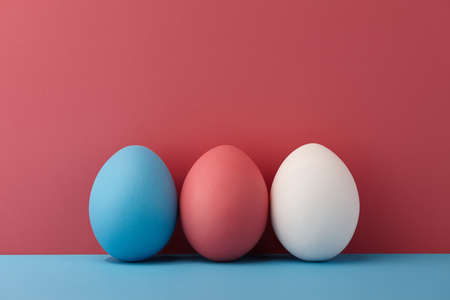 Painted Easter eggs on pink and blue background, spring holiday preparation Standard-Bild