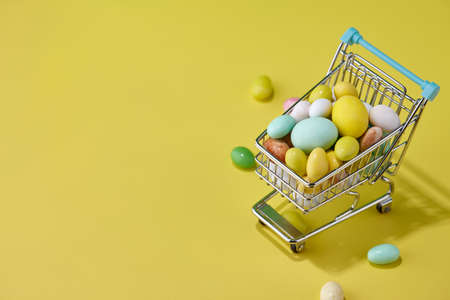 Colorful Easter sweets in shopping basket on yellow background, holiday concept