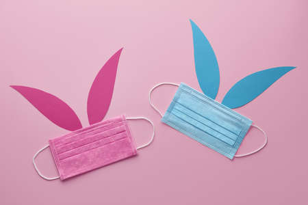 Easter bunnies made from blue and pink protective face masks. Holiday creative concept. Standard-Bild