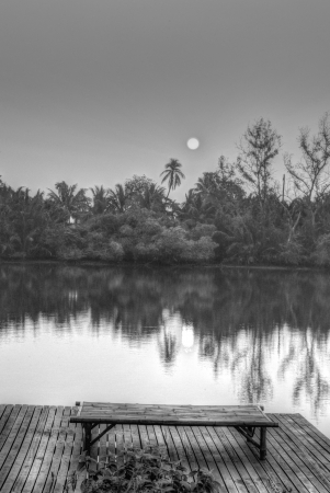 Black and White Lanscape of Misty Morning Countryside with Sunrise, River, Boat, Coconut Tree and Garden.Chachoensao province,Thailand. Stock Photo