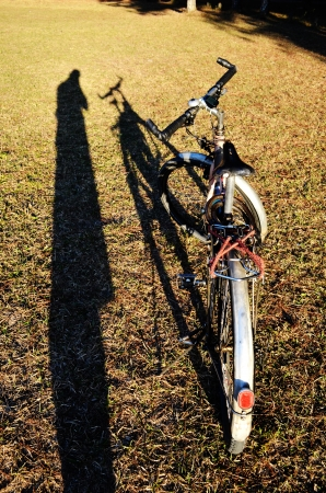 A Shadow man and Bicycle in the sun. Stock Photo