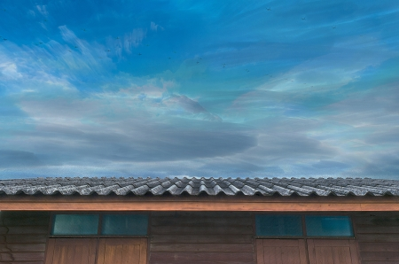 The Moving Planes, Cloudy Blue Sky and Roof of Wooden House. Stock Photo