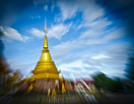 The Thai Golden Phra Tad or Pagoga with Blue Cloudy Sky and Zooming Technique. Stock Photo