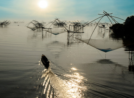The Fisherman Boat and Square Fish Net in Morning Sunrise at Songkla Lake Thailand.