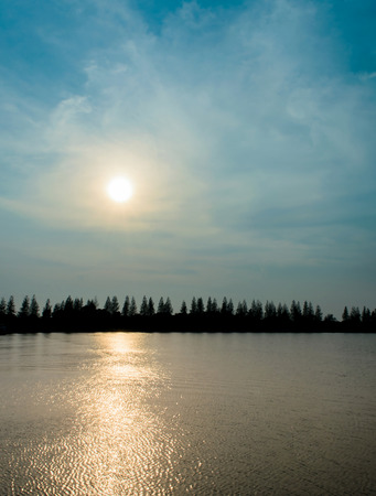 The Silhouette Pine Tree and Reflection Sunset on River in Thailand. Stock Photo