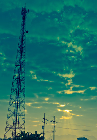 The Communication Antenna Tower and Cloudy Sky with Sunbeam in the Morning.
