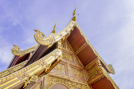 The Buddhist Temple Art with Naga Structure on Gable and Blue Sky in Thailand.