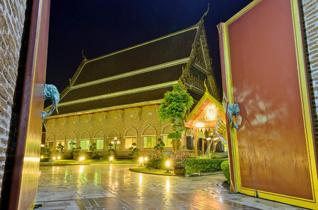 The Wooden Door and Golden Buddhist Temple at Night. Stock Photo