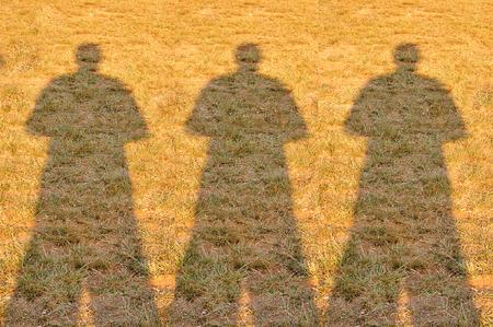 The Shadow of Three Photographer Man on Field.