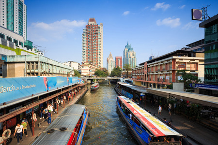 water transportation: Bangkok, Thailand - February 8, 2015: Skyscraper and boat pier in Bangkok; water transportation by canal speed boat is one of the alternative choice for solving the traffic congestion problem in Bangkok. Editorial