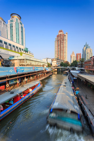 water transportation: Bangkok, Thailand - February 8, 2015: Skyscraper and boat pier in Bangkok; water transportation by  speed boat is one of the alternative choice for solving the traffic congestion problem in Bangkok.