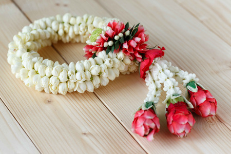 seniority: Image of Flower garlands in thai style on the wood background, it is used for giving to Buddha, parent, teacher or seniority people to show love and respect.