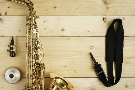 strap on: Saxophone on the wood background with strap, mouse and mute