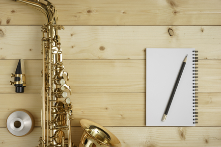 woodwind instrument: Saxophone on the wood background with mouse, mute, pencil and notebook