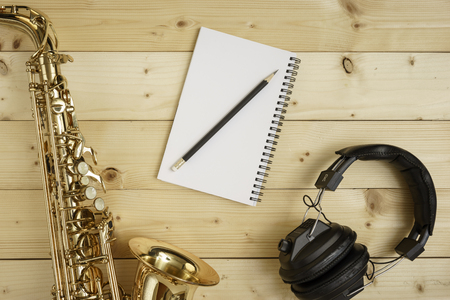 woodwind instrument: Saxophone on the wood background with pencil, notebook and headphones
