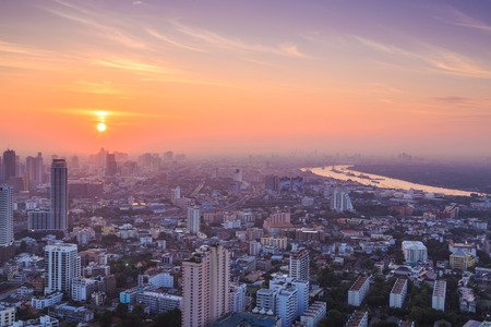 thai culture: Bangkok cityscape in the morning, view from high building, sun is rising and mist is covering the city