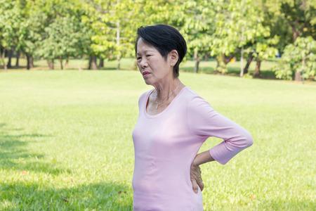 公園でアジアのシニア女性の背中痛み