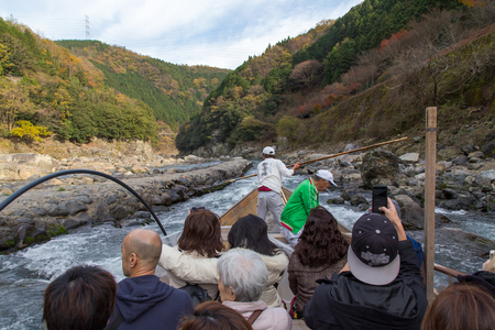2 way: Kyoto, Japan - December 2, 2015: Hozugawa River Cruises are sightseeing boat rides down the Hozugawa River from Kameoka to Arashiyama. Tourists can take a boat  about two hours to leisurely make their way down the river and are a relaxing way to see the n