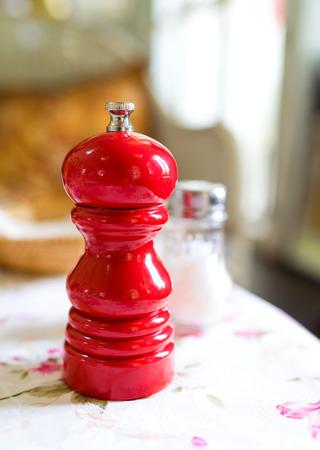 Rote Pfeffermühle und Salz Flasche auf dem Hintergrund