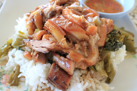 Stewed pork leg on cooked rice with vegetable ready to serve.