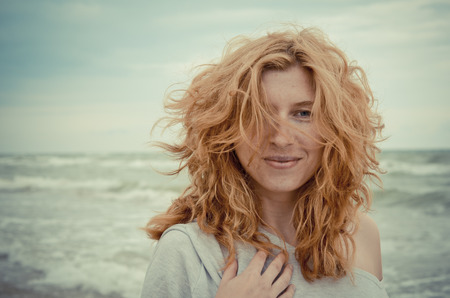 Portrait of fancy and beautiful red-haired girl on the seaside. photo