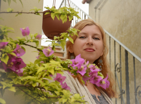 redhaired: Portrait of a pretty red-haired woman behind the pink flowers Stock Photo