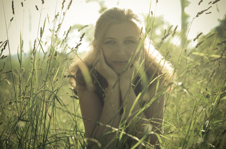redhaired: Portrait of a red-haired beautiful woman in the grass and spikelets