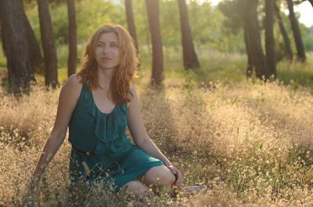 tail woman: Retrato de una bella mujer de pelo rojo en el vestido verde que se sienta en la hierba cola del conejito Foto de archivo