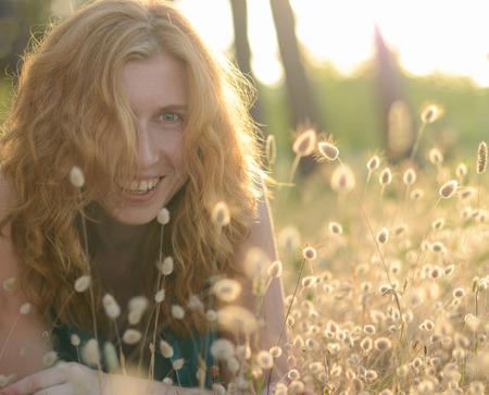 tail woman: Retrato de una hermosa mujer feliz pelirrojo en la hierba cola del conejito