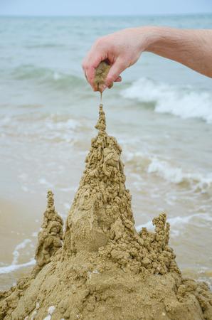 builds: Mans hand builds a sandcastle