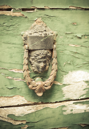 heads old building facade: Ancient door handle in head shape on flaked green door