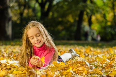 lying on leaves: Autumn portrait of curly smiling girl lying on yellow leaves Stock Photo