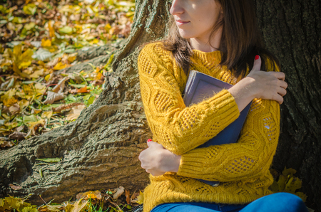bookish: Autumn portrait of girl leaning on a tree trunk whose hands hug the book