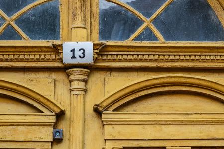 thirteen: Ancient yellow door with number thirteen