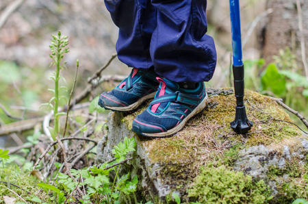 childs feet stand on a rocky mountain trail