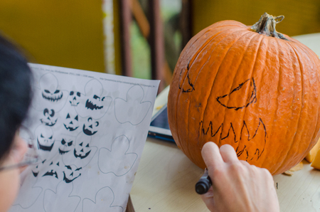 Drawing on pumpkins for Halloween party
