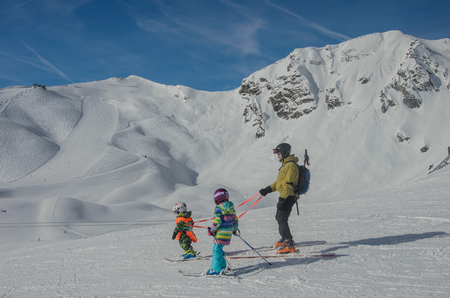 Stunning view of the mountains and skiers family in Obertauern ski resort